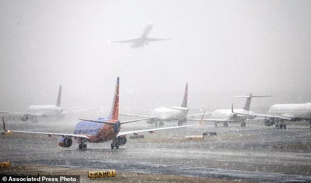 Planes line up on the tarmac as snow falls delaying travel at Hartsfield-Jackson Atlanta International Airport Friday, 8 December 2017, in Atlanta. Photo: Bob Andres / Atlanta Journal-Constitution / AP