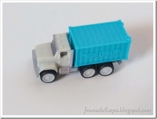 Close up of the toy truck, it's light blue and gray.