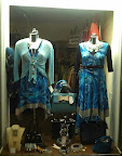 primarily blue lit shop window display of clothing & accesories