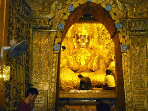 "Photo: According to legend, Buddha visited near here in 554 BC.  King Thuriya requested that an image be cast of him. After casting the Great Image, the Buddha breathed upon it, and thereafter the image became the exact likeness.  Men could achieve ""merit"" by adding gold leaf to Buddha.  With about two tons of gold leaf on it, the Buddha has lost its shape."