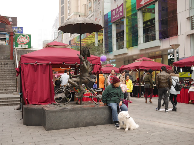 elderly woman with white dog sitting next to a statue of a woman riding a bicycle at the Wujiang Road Pedestrian Street