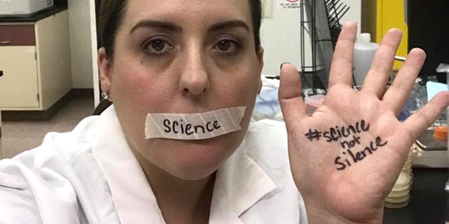 A scientist wears a gag and has #ScienceNotSilence written on her palm, to protest Trump antiscience policies. Photo: EcoWatch