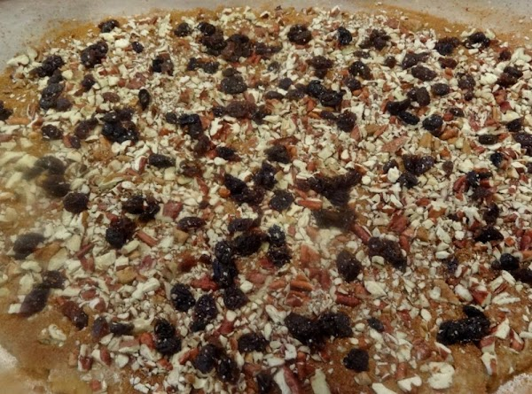 Spread the pecans and raisins evenly over the cinnamon mixture and press gently down...