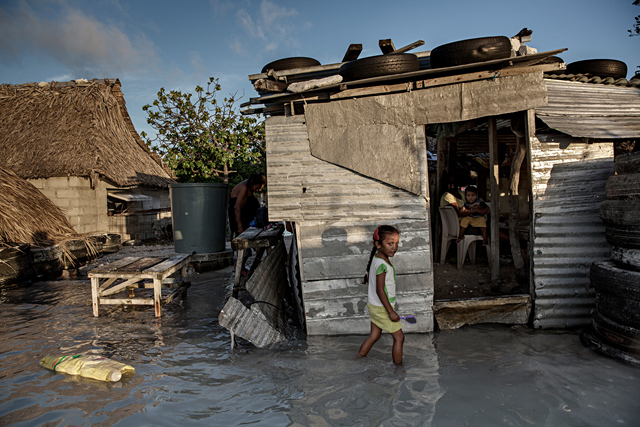A young girl wades through the incoming sea water that flooded her house and village in Kiribati, 30 September 2015. Photo: Jonas Gratzer / LightRocket