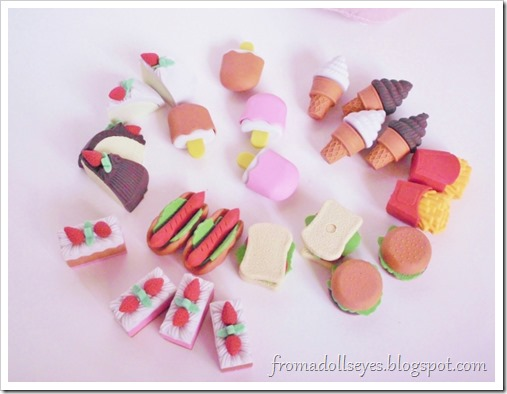 A nicely arranged assortment of food shaped erasers including, ice cream cones, other frozen treats, cakes, hot dogs, sandwiches, hamburgers and french fries.
