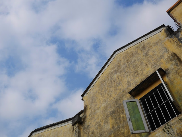 open window of a yellow building with a blue sky and cloud above in Shimen Village, Shaxi Town, Zhongshan