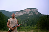 "Crow Reservation. Bubba Pisano poses for photo in front of mountain. His shirt reads""Homeland Security: Fighting Terrorism Since 1492."" The t-shirt shows a historical photo of Natives holding rifles.  Bubba travels with his guns in case he may be able to hunt. Later that night the family was able to shoot a deer for food."