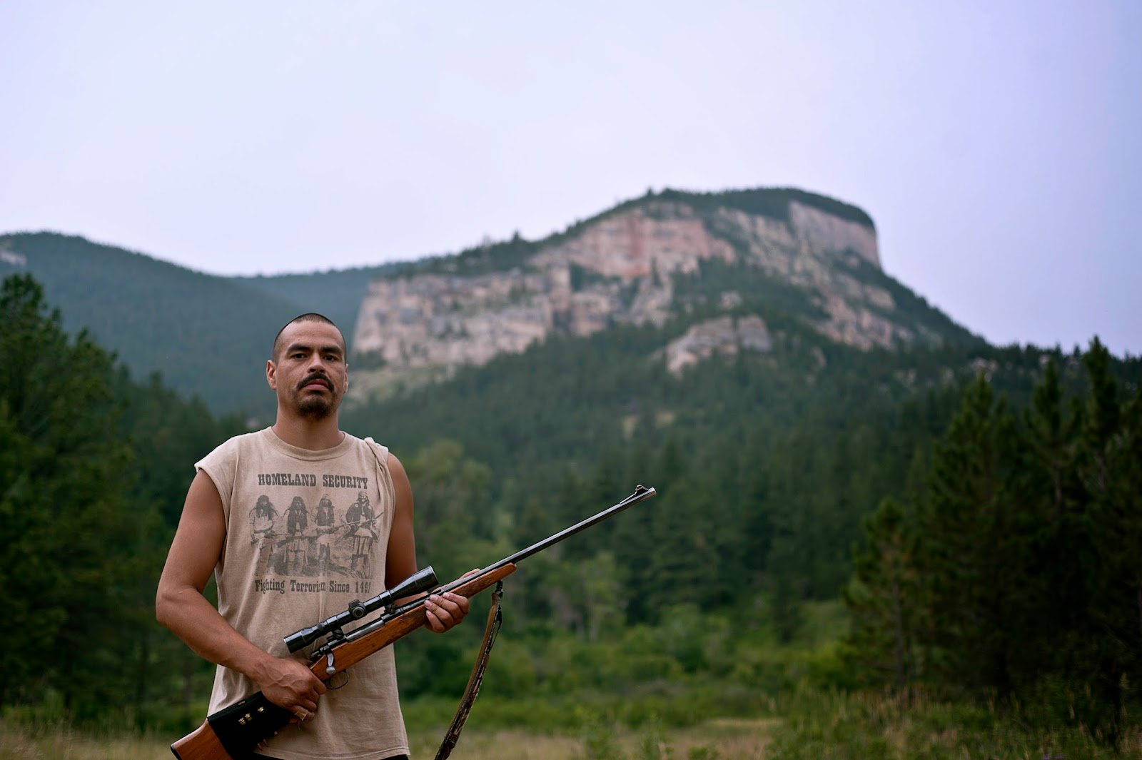 """Crow Reservation. Bubba Pisano poses for photo in front of mountain. His shirt reads""""Homeland Security: Fighting Terrorism Since 1492."""" The t-shirt shows a historical photo of Natives holding rifles.  Bubba travels with his guns in case he may be able to hunt. Later that night the family was able to shoot a deer for food."""