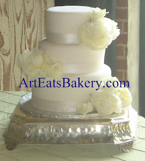 Three tier white fondant unique wedding cake design with fresh peones and roses. and hand painted pearl ribbons