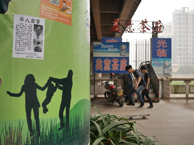 missing person sign and boys skateboarding in the background in Jieyang, China