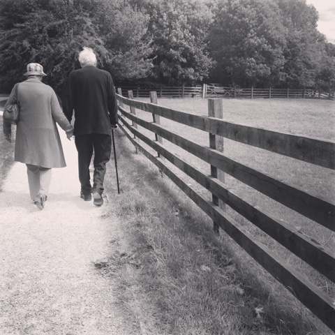 An old couple walking holding hands