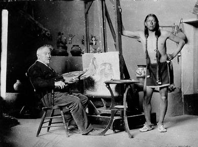 Couse seated in his studio with Ben Luhan, a Taos Pueblo Indian