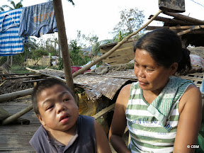 A woman and a young boy sitting among broken buildings and drying clothes