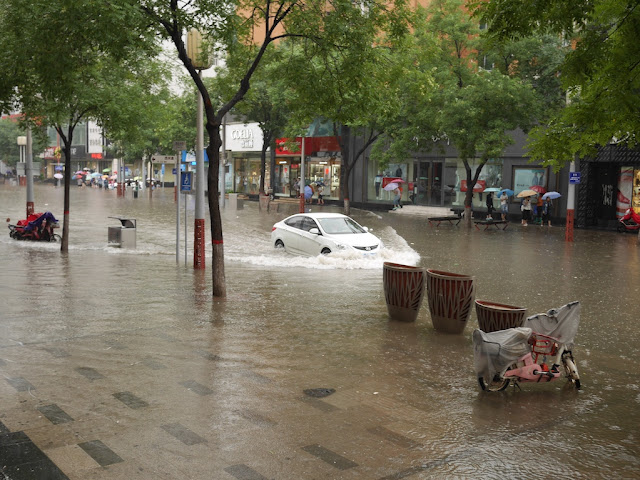 Car driving on a flooded street in Taiyuan, China