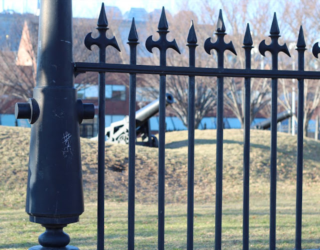 view of cannon in Fort Washington Park through iron fence