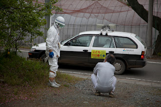 Photo: May 7, 2011. Odaka, Fukushima, Japan. Kobayashi invites me to stay in his home. His brother, shown here on the left, works for the Minami-soma government, and stops by each morning to perform a radiation reading of the property. His dosimeter is shown hanging from his neck.