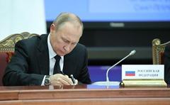Vladimir Putin signing documents at the Supreme Eurasian Economic Council.