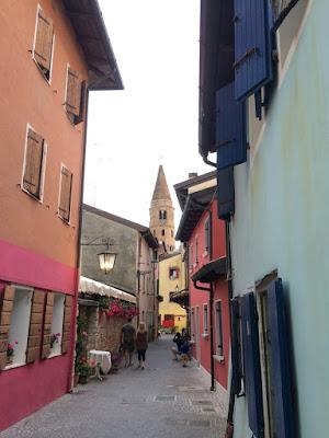 En trang gate mellom fargerike hus med et tårn i det fjerne.