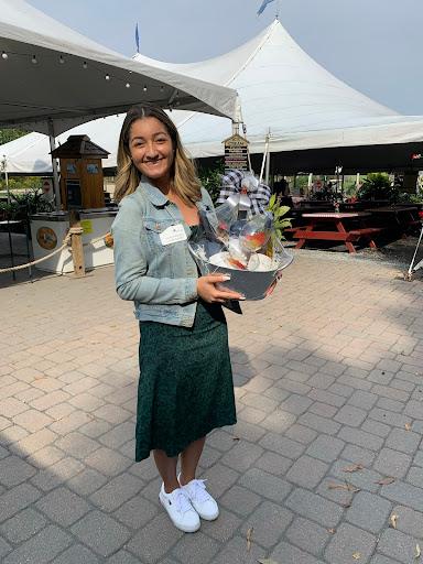 Sarah Marinho, an employee at 50 West Broadway, posing with the gift basket she won