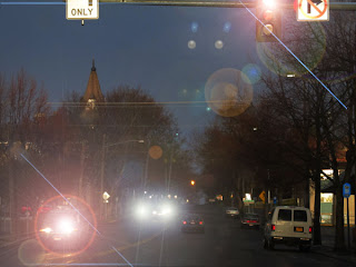 same street scene with less ambient light and lens flare on the headlights of all the cars, representing glare