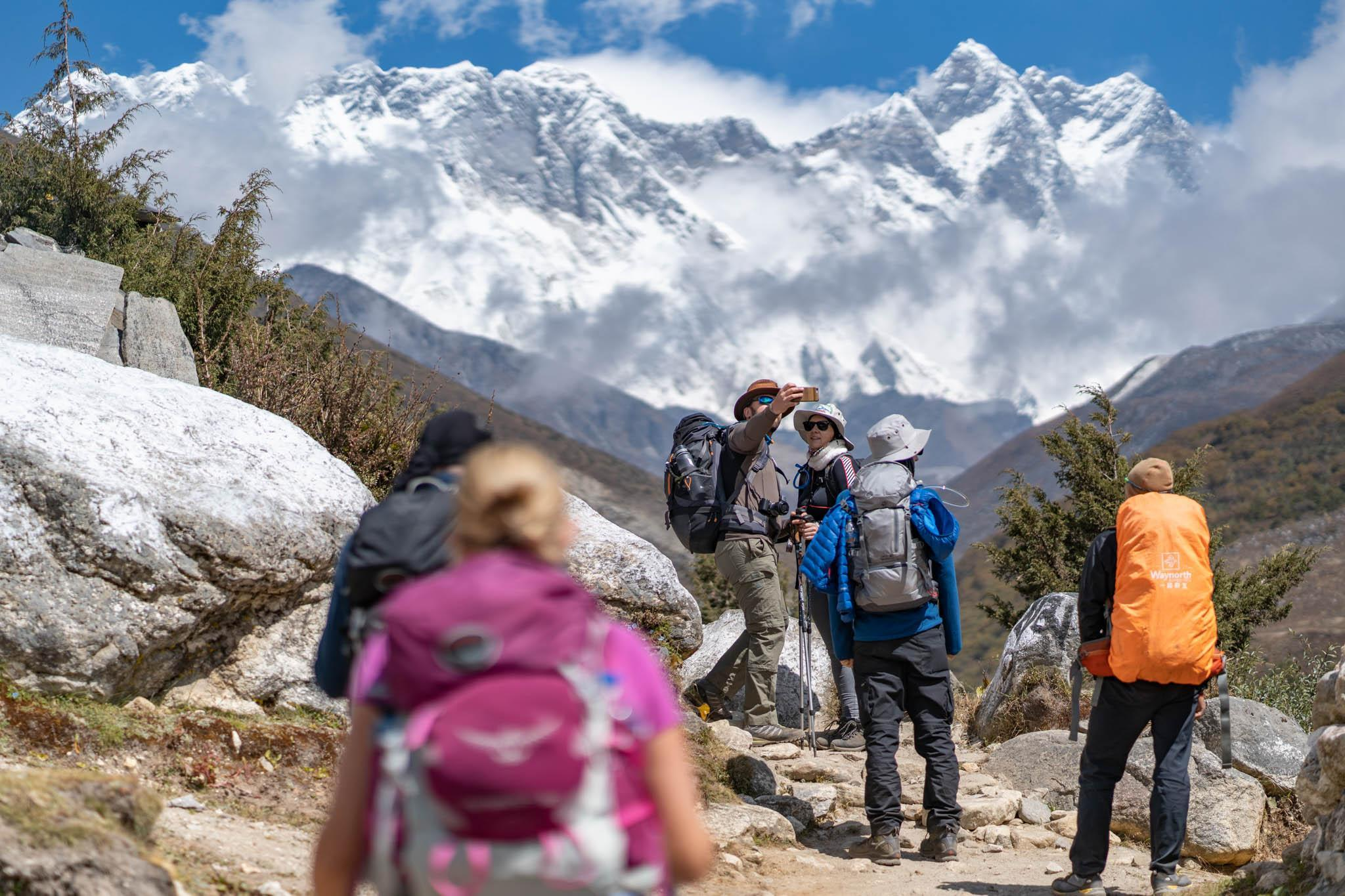 A group of hikers looking at the mountain and taking pictures