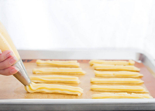 photo of churro dough being piped onto a baking sheet