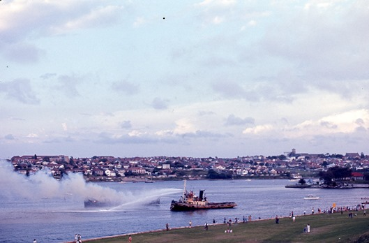 John-Ward-Sydney-Ferries-ferry-Lady-Scott-on-fire-in-Iron-Cove-off-shore-at-Drummoyne,-Sydney,-New-South-Wales,-Australia