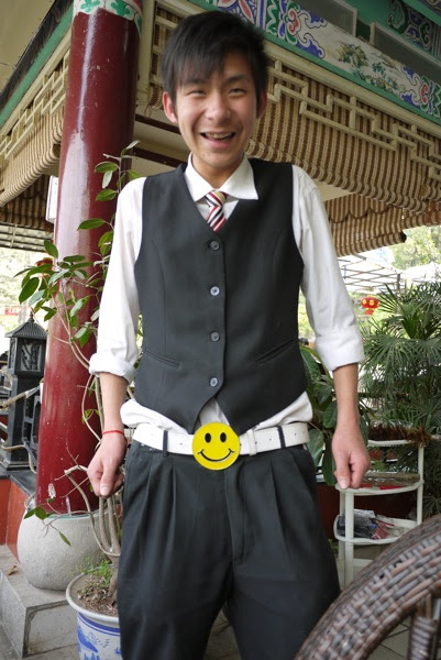 Chinese waiter in formal attire with a large yellow happy face belt buckle