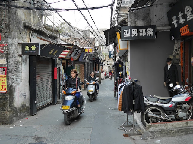 young woman on a motorbike riding by small stores in Yangjiang, China