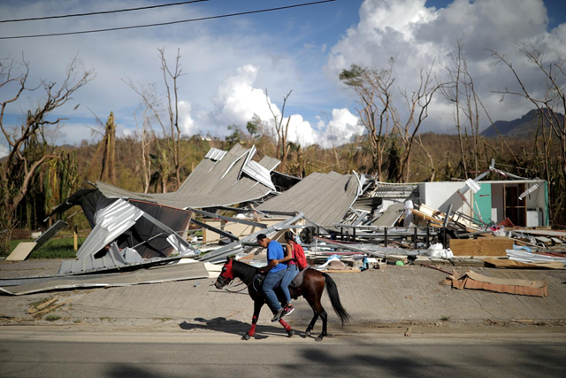 Local residents ride a horse by a destroyed building after Hurricane Maria in Jayuya, Puerto Rico 4 October 2017. Photo: REUTERS