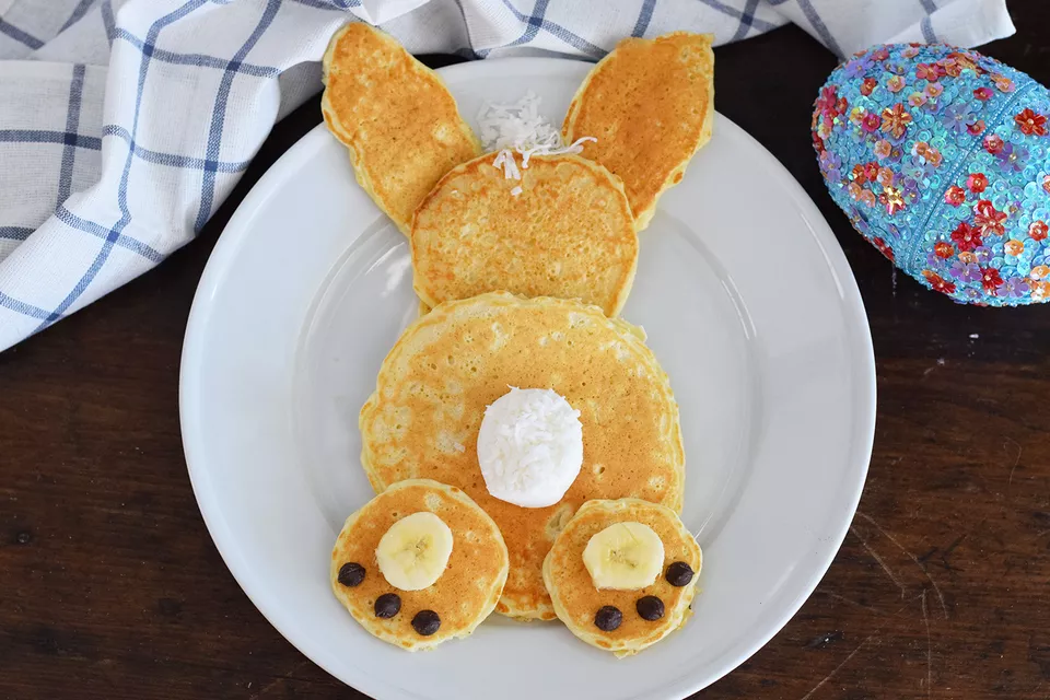 Six pancakes of various shapes and sizes assembled in the shape of a bunny. Includes banana and chocolate chip toes, and a marshmallow tail.