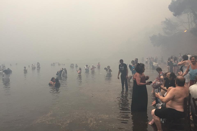 People fled into the sea to seek safety from the wildfires in Mati, Greece, 23 July 2018. Photo: Nikos Kalogerikos / Reuters
