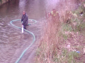 man in waders struggling with large hose and reeds