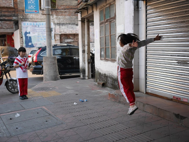 girl leaping backwards in a game in Shaoguan, Guangdong