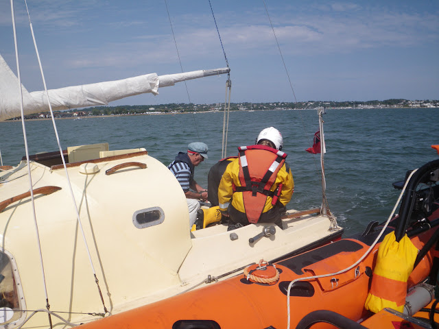 3 August 2011 - Poole inshore lifeboat Helmsman replacing a fuel line to the inside of the fuel tank ono a 6.5m catamaran after towing it back into Poole Harbour (Photo: RNLI/Poole Lifeboat Station)