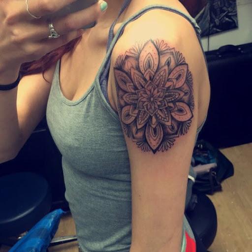 Uma incrivel especie de arte da tatuagem no ombro de uma mulher