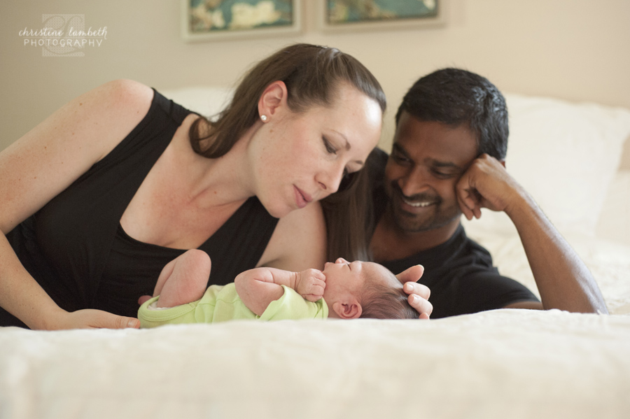 New parents with newborn on bed