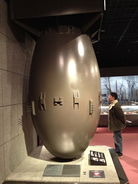 A man looks at a statue of the bomb