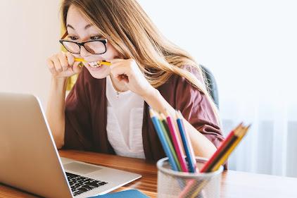 Woman biting a pencil looking at a laptop