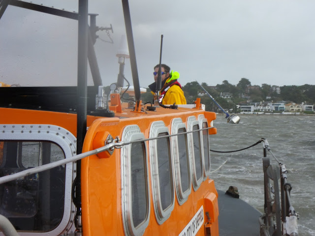 A volunteer crew member keeps a lookout as the ALB tows the stricken yacht - 27 October 2013. Photo credit: RNLI Poole