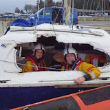 Two crew members peer out of the stricken catamaran at Rockley - 24 December 2013.  Photo credit: RNLI/Poole