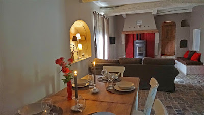 Salle à mangée composée d'une table pouvant recevoir 12 personnes, d'un canapé d'angle, une télévision écran plat et  un poêle à granules.