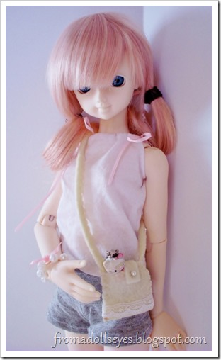 A ball jointed doll carrying her favorite Hello Kitty toy in her purse.