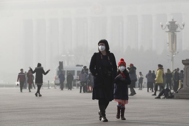 A foreign tourist and a child wearing protection masks walk through Tiananmen Square in Beijing as the capital of China is blanked by heavy smog on Wednesday, 4 January 2017. China has long faced some of the worst air pollution in the world, blamed on its reliance of coal for energy and factory production, as well as a surplus of older, less efficient cars on its roads. Inadequate controls on industry and lax enforcement of standards have worsened the pollution problem. Photo: Andy Wong / AP Photo