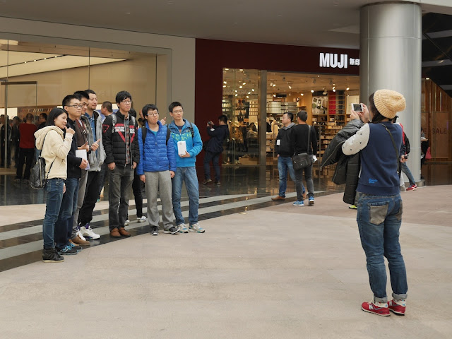 group posing for a photo in front of the SM Lifestyle Center Apple Store in Xiamen, China