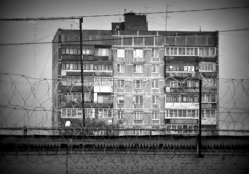 passing by a Soviet bloc-apartment building, which rises behind the barbed wires of the local prison!