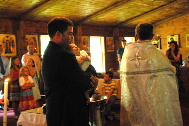 The newly-baptized Alexander is led around the font three times, a symbol of his union to the church.