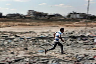 A Palestinian man runs when he hears an Israeli tank movement from its position behind the hill, close to the border with Israel, as he return to inspect damage to his house during a 12-hour cease-fire in Beit Hanoun, northern Gaza Strip, Saturday, July 26, 2014. Thousands of Gaza residents who had fled Israel-Hamas fighting streamed back to devastated border areas during a lull Saturday to find large-scale destruction: scores of homes were pulverized, wreckage blocked roads and power cables dangled in the streets. (AP Photo/Lefteris Pitarakis)