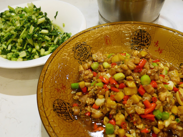spicy dish and greens with portion of a metal rice bucket visible