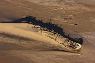 Photo: The Skeleton Coast is an infamous stretch of coastline running down the south of Angola and northern Namibia. The combination of heavy surf, thick fogs and inhospitable desert have over the years led to more than a thousand shipwrecks and many lost lives. This, combined with the bleached whale and seal bones that covered the shores in the days when whaling was active are what gave the area its name.  This is one of the many shipwrecks I saw during an aerial flight along the coast. This particular wreck was the Eduard Bohlen, situated about 200m 400m inland (thanks Wikipedia! http://en.wikipedia.org/wiki/Eduard_Bohlen) as a result of the constantly shifting sands. I can only imagine how out of place it must look from ground level where the sea wouldn't be visible, though I can't imagine getting to it over ground would be very easy!  Here's its location on Google Maps: http://g.co/maps/z2hc7